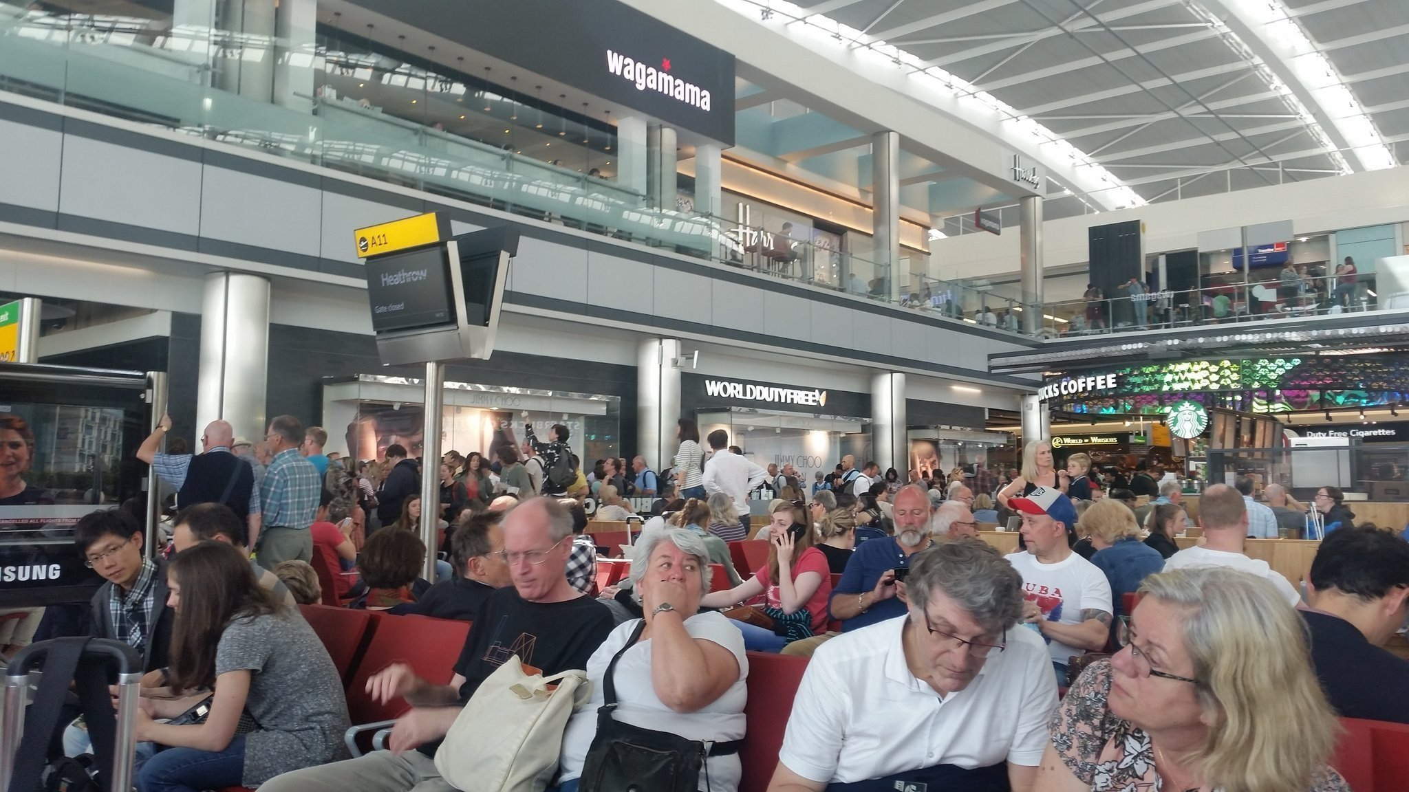 Caption: Waiting area at Heathrow airport where passengers are waiting for details about flights.